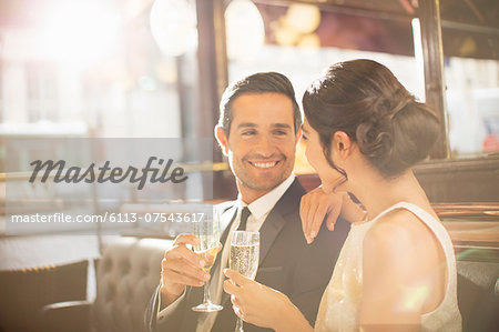 Couple drinking champagne in restaurant Stock Photo - Premium Royalty-Free, Image code: 6113-07543617