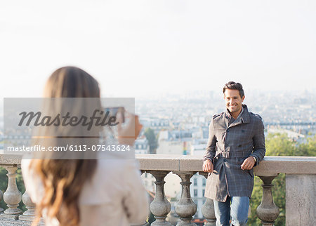 Woman photographing boyfriend with Paris in background Stock Photo - Premium Royalty-Free, Image code: 6113-07543624