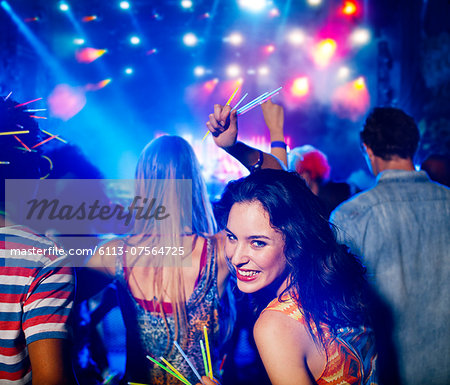 Woman with glow sticks at music festival Stock Photo - Premium Royalty-Free, Image code: 6113-07564725