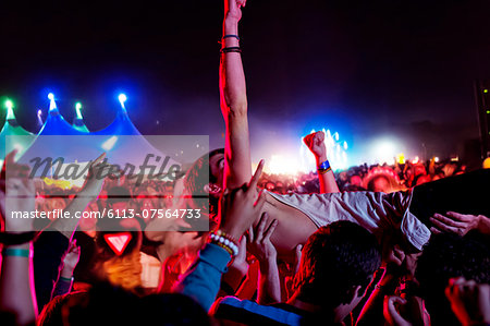 Man crowd surfing at music festival Stock Photo - Premium Royalty-Free, Image code: 6113-07564733