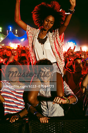Cheering woman on man's shoulders at music festival Stock Photo - Premium Royalty-Free, Image code: 6113-07564773