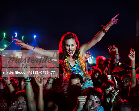 Cheering woman on man's shoulders at music festival Stock Photo - Premium Royalty-Free, Image code: 6113-07564774