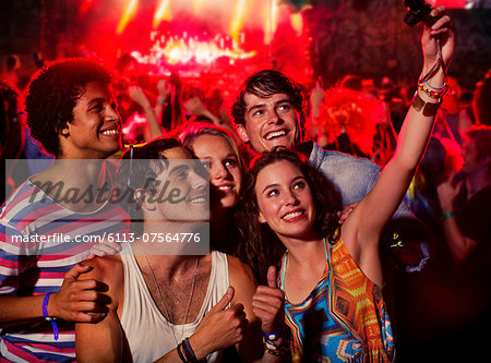 Friends taking self-portrait with camera phone at music festival Stock Photo - Premium Royalty-Free, Image code: 6113-07564776
