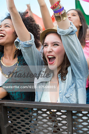 Woman cheering at music festival Stock Photo - Premium Royalty-Free, Image code: 6113-07564805