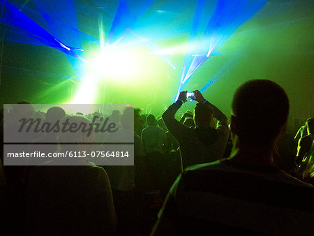 Silhouette of crowd facing illuminated stage at music festival