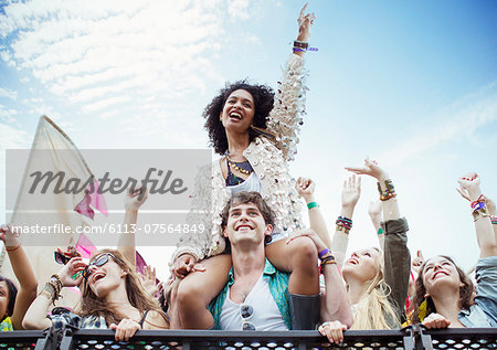 Cheering woman on man's shoulders at music festival Stock Photo - Premium Royalty-Free, Image code: 6113-07564849