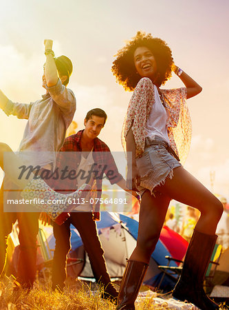 Friends dancing outside tents at music festival Stock Photo - Premium Royalty-Free, Image code: 6113-07564891
