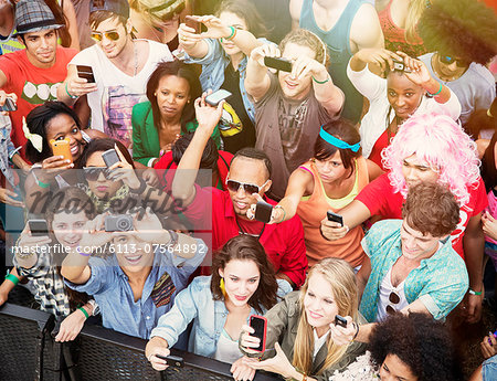 Fans with camera phones cheering at music festival Stock Photo - Premium Royalty-Free, Image code: 6113-07564892