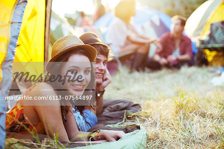 Portrait of couple laying in tent at music festival Stock Photo - Premium Royalty-Free, Image code: 6113-07564897