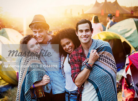 Portrait of couples wrapped in a blanket outside tents at music festival Stock Photo - Premium Royalty-Free, Image code: 6113-07564900