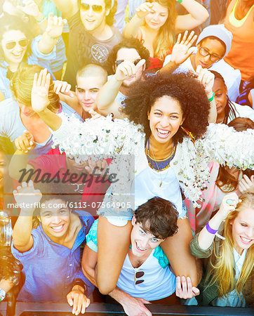 Portrait of cheering woman on man's shoulders at music festival Stock Photo - Premium Royalty-Free, Image code: 6113-07564905