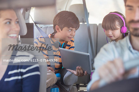 Brother and sister sharing digital tablet in back seat of car Stock Photo - Premium Royalty-Free, Image code: 6113-07564930