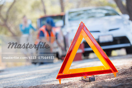 Warning triangle on road with mechanic in background Stock Photo - Premium Royalty-Free, Image code: 6113-07564933