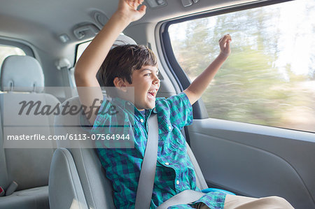Enthusiastic boy cheering in back seat of car Stock Photo - Premium Royalty-Free, Image code: 6113-07564944
