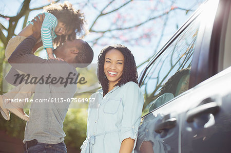 Portrait of happy woman with husband and daughter outside car Stock Photo - Premium Royalty-Free, Image code: 6113-07564957
