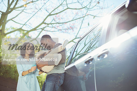 Happy family outside car Stock Photo - Premium Royalty-Free, Image code: 6113-07565000