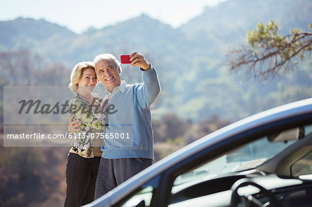 Senior couple taking self-portrait with cell phone outside car Stock Photo - Premium Royalty-Free, Image code: 6113-07565001