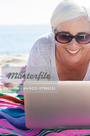 Happy woman using laptop on beach Stock Photo - Premium Royalty-Free, Image code: 6113-07565151