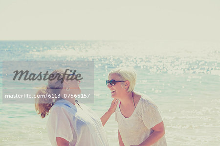 Women laughing on sunny beach Stock Photo - Premium Royalty-Free, Image code: 6113-07565157