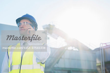 Worker talking on cell phone at granary Stock Photo - Premium Royalty-Free, Image code: 6113-07565338