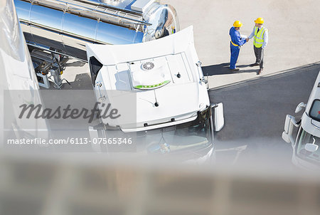 Workers handshaking next to stainless steel milk tanker Stock Photo - Premium Royalty-Free, Image code: 6113-07565346