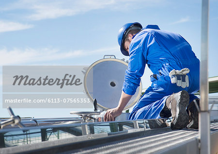 Worker on platform looking down at milk tanker Stock Photo - Premium Royalty-Free, Image code: 6113-07565353