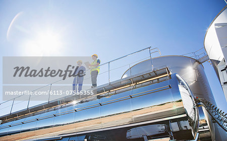 Workers on platform above stainless steel milk tanker Stock Photo - Premium Royalty-Free, Image code: 6113-07565355