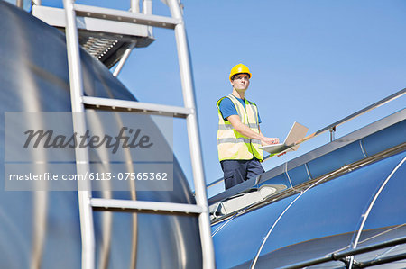Worker using laptop on platform above stainless steel milk tanker Stock Photo - Premium Royalty-Free, Image code: 6113-07565362