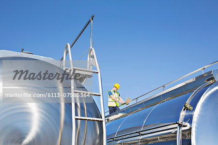 Worker using laptop on platform above stainless steel milk tanker Stock Photo - Premium Royalty-Free, Image code: 6113-07565364