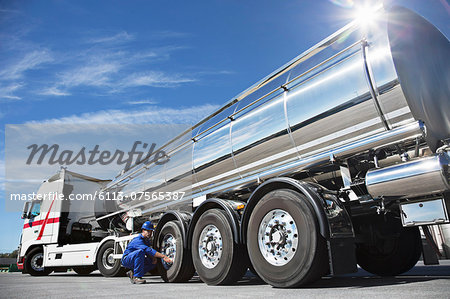 Worker checking tire on stainless steel milk tanker Stock Photo - Premium Royalty-Free, Image code: 6113-07565387