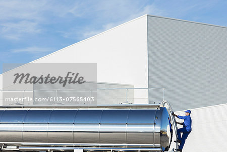 Worker climbing ladder at back of stainless steel milk tanker Stock Photo - Premium Royalty-Free, Image code: 6113-07565403