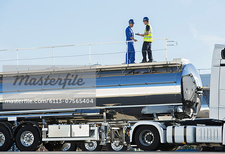 Workers on platform above stainless steel milk tanker Stock Photo - Premium Royalty-Free, Image code: 6113-07565404