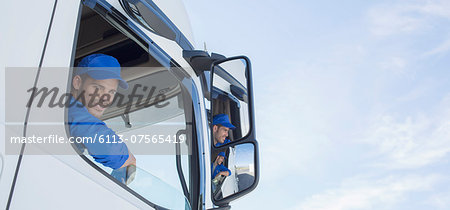 Portrait of smiling truck driver leaning out window Stock Photo - Premium Royalty-Free, Image code: 6113-07565419