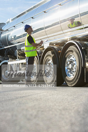 Worker with clipboard checking stainless steel milk tanker Stock Photo - Premium Royalty-Free, Image code: 6113-07565422