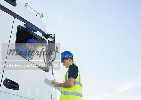 Worker with clipboard talking to truck driver Stock Photo - Premium Royalty-Free, Image code: 6113-07565425