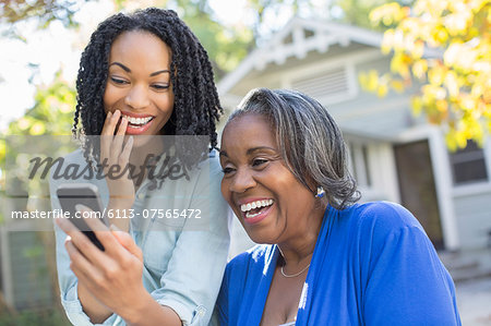 Mother and daughter looking at cell phone and laughing Stock Photo - Premium Royalty-Free, Image code: 6113-07565472