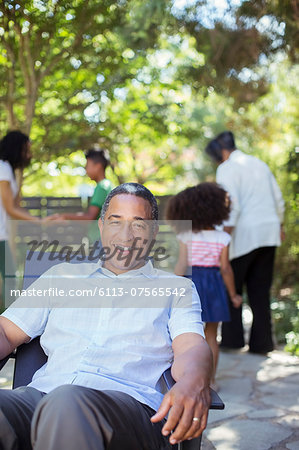 Portrait of smiling senior man on patio with family in background