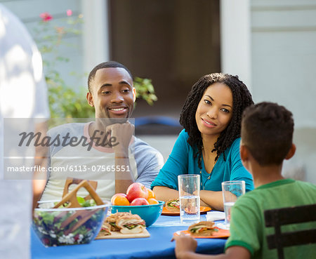 Family eating lunch at patio table Stock Photo - Premium Royalty-Free, Image code: 6113-07565551