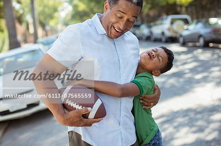 Grandson tackling grandfather with football Stock Photo - Premium Royalty-Free, Image code: 6113-07565559