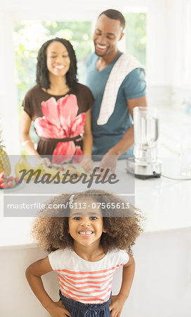 Portrait of enthusiastic girl in kitchen with parents in background Stock Photo - Premium Royalty-Free, Image code: 6113-07565613