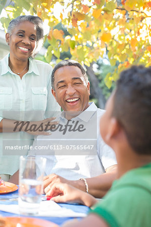 Grandparents and grandson laughing at patio table Stock Photo - Premium Royalty-Free, Image code: 6113-07565647
