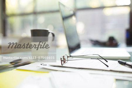 Close up of coffee cup and eyeglasses on paperwork near laptop Stock Photo - Premium Royalty-Free, Image code: 6113-07565655