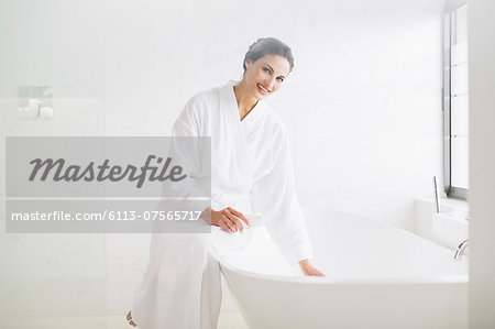 Portrait of smiling woman in bathrobe preparing bath Stock Photo - Premium Royalty-Free, Image code: 6113-07565717