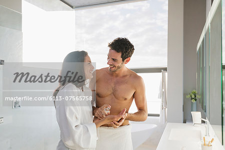 Man dispensing moisturizer in woman's hand Stock Photo - Premium Royalty-Free, Image code: 6113-07565758