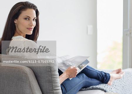 Portrait of confident woman reading magazine on chaise lounge Stock Photo - Premium Royalty-Free, Image code: 6113-07565792
