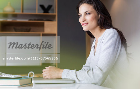 Confident woman sitting at table Stock Photo - Premium Royalty-Free, Image code: 6113-07565805