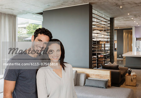 Portrait of happy couple in living room Stock Photo - Premium Royalty-Free, Image code: 6113-07565818