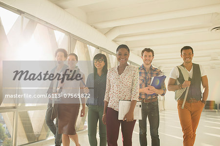 Confident creative business people walking in sunny corridor Stock Photo - Premium Royalty-Free, Image code: 6113-07565872