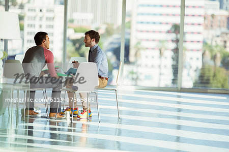 Creative businessmen meeting at circle of chairs in sunny office Stock Photo - Premium Royalty-Free, Image code: 6113-07565883