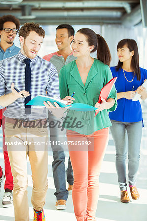 Creative business people with folders walking in office corridor Stock Photo - Premium Royalty-Free, Image code: 6113-07565892